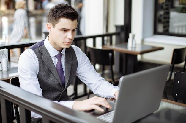 Bem sucedido jovem empresário digitando no laptop no café Foto Premium