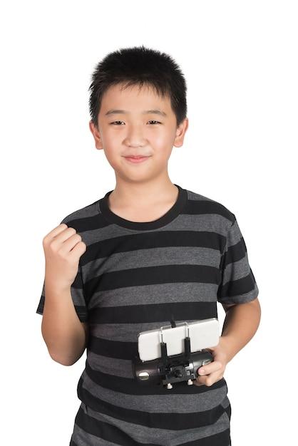 Bem sucedido rapaz asiático feliz segurando o controle remoto de rádio para drone Foto Premium
