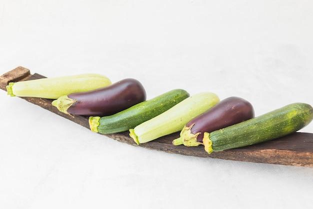 Beringelas colhidas inteiras coloridas na bandeja de madeira contra o fundo branco Foto gratuita