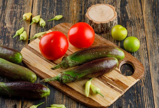 Beringelas com tomates, pimentos, ameixas verdes, madeira na tábua de madeira e corte, vista de alto ângulo. Foto gratuita
