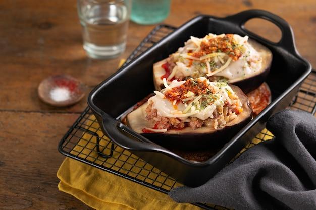 Berinjela assada recheada, brinjal ou berinjela com carne e legumes Foto Premium