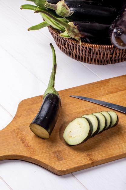 Berinjela picada vista frontal em uma placa com uma faca com berinjela fresca em uma cesta Foto gratuita