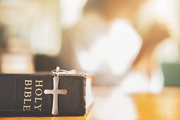 Bíblia sagrada e cruz na mesa com a mulher cristã esperando para melhor. Foto Premium
