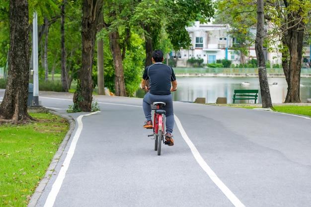 Bicicleta da equitação do homem do esporte na estrada no parque. Foto Premium