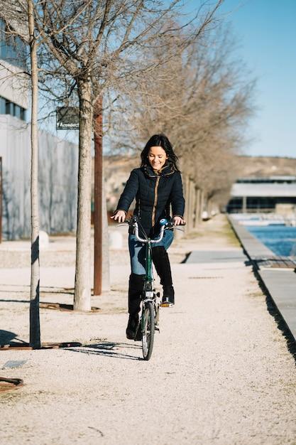 Bicicleta de equitação mulher moderna na cidade Foto gratuita