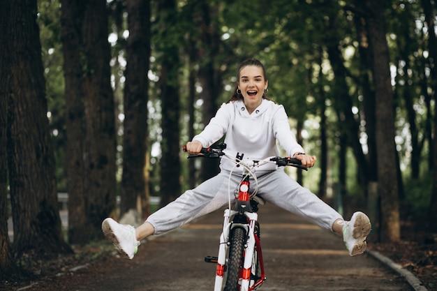 Bicicleta desportiva nova da equitação da mulher no parque Foto gratuita