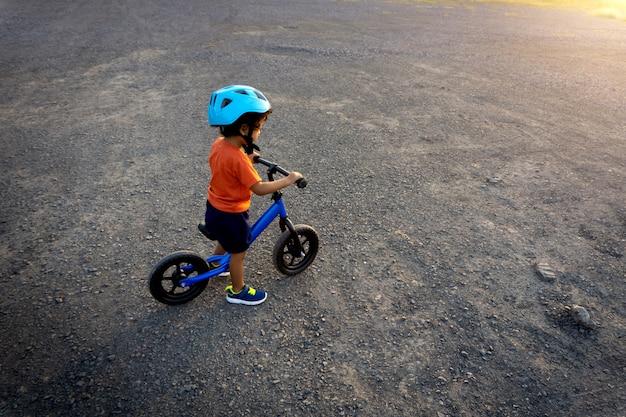 Bicicleta do equilíbrio do jogo do dia da criança asiática primeira. Foto Premium