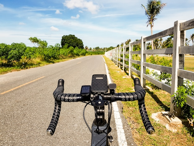 Bicicleta estacionada ao lado da estrada aberta com céu azul Foto Premium