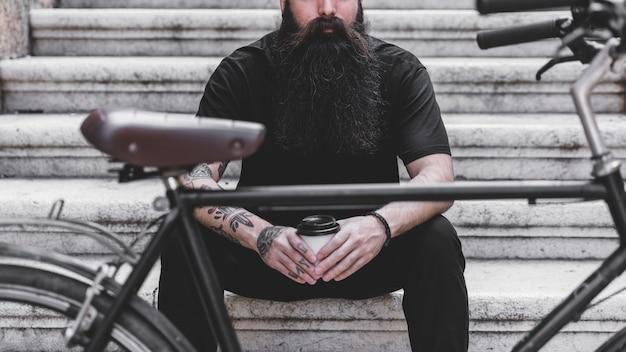 Bicicleta, frente, homem jovem, sentando, ligado, escadaria, segurando, copo café descartável Foto gratuita