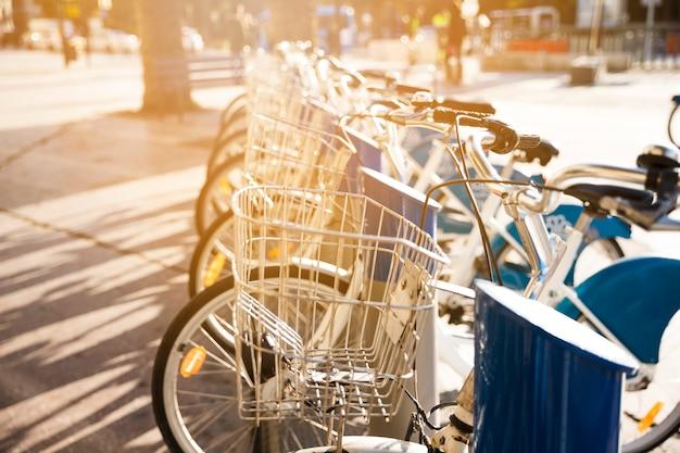 Bicicletas da cidade com cesta de metal para alugar ficar em uma fila em uma rua de paralelepípedos Foto gratuita