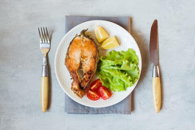 Bife assado peixe salmão em um prato com legumes frescos. Foto Premium