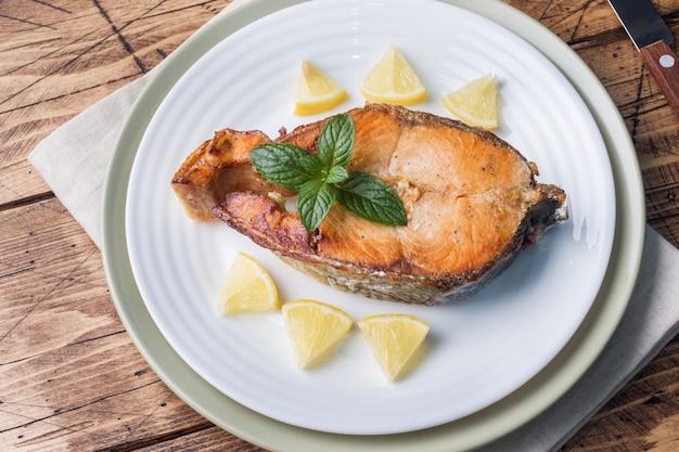 Bife assado peixe salmão em um prato com limão. mesa de madeira. Foto Premium