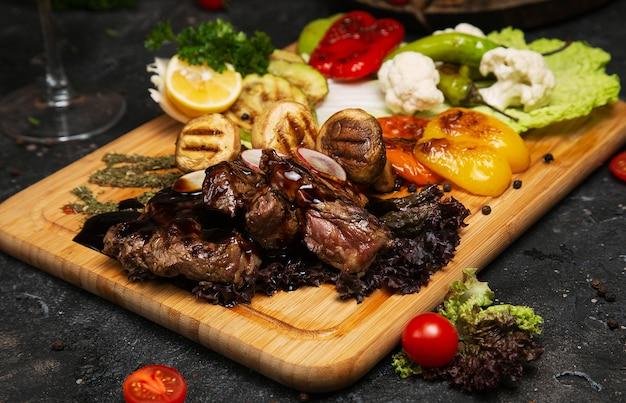 Bife club com molho de pimenta e legumes grelhados na tábua de cortar Foto gratuita