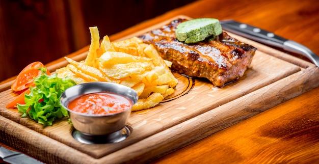 Bife com molho de pimenta e legumes grelhados na tábua Foto Premium