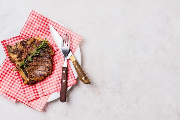 Bife com osso no prato Foto gratuita