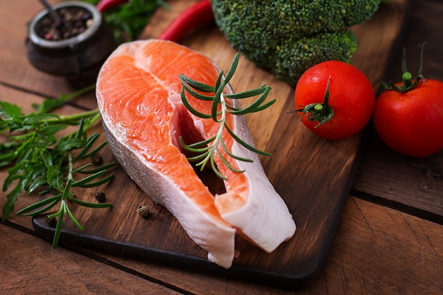 Bife cru salmão e legumes para cozinhar na mesa de madeira em estilo rústico. Foto gratuita