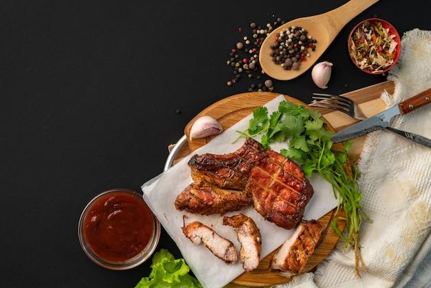 Bife de bife ribeye grelhado, folhas de ervas e especiarias ao redor, vista superior com espaço de cópia para seus textos Foto Premium