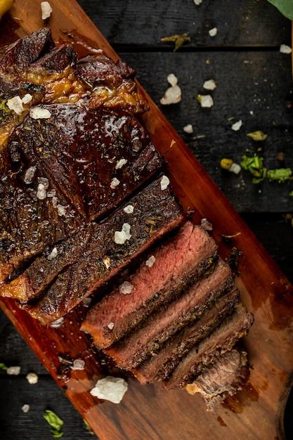 Bife de carne cozida crua fatiada e adicionado de sal, servido na mesa preta Foto gratuita