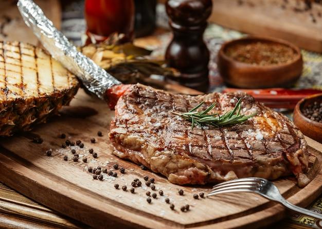 Bife de carne em um prato de madeira com pimenta preta e alecrim. Foto gratuita