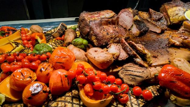 Bife de churrasco saboroso com tomate, pimentão e cebola na grelha pan close-up em cima da mesa Foto Premium