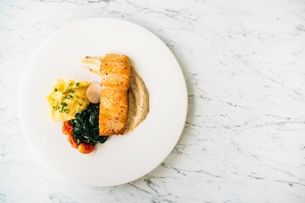 Bife de filé de salmão grelhado com legumes e molho Foto gratuita