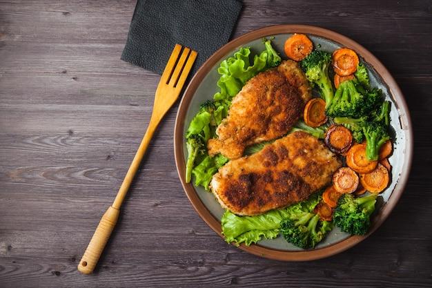 Bife de frango na farinha de rosca com legumes em um prato Foto Premium