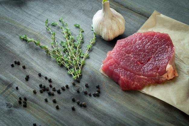 Bife de lombo cru com alho e tomilho na mesa de madeira escura Foto Premium