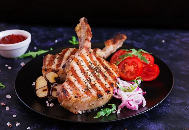 Bife de porco cru com ervas na superfície escura. bife suculento cru no osso Foto Premium