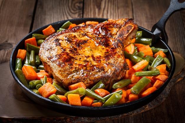 Bife suíno com feijão verde e cenouras em panela de ferro