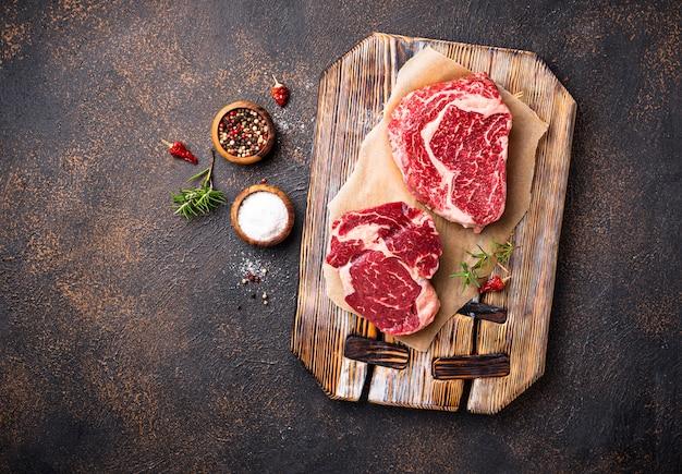 Bife de ribeye marmoreado cru e especiarias Foto Premium