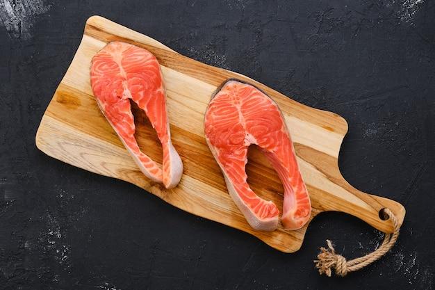 Bife de salmão fresco cru na tábua de madeira Foto Premium