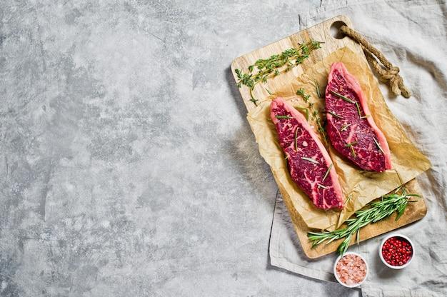Bife do lombo da carne em uma placa de desbastamento de madeira com alecrins e pimenta cor-de-rosa. copyspace Foto Premium