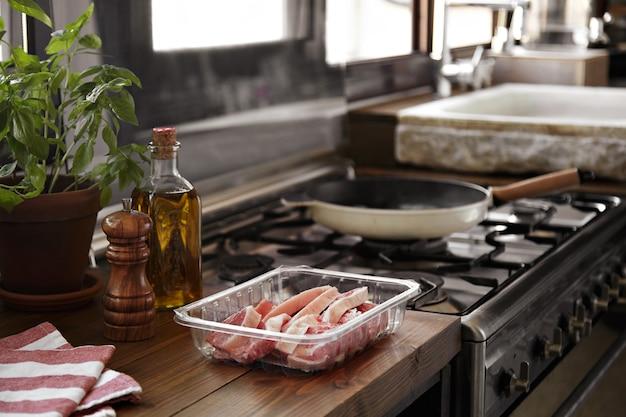 Bife fatiado prestes a ser grelhado em uma panela ao lado de uma cozinha com janela Foto gratuita