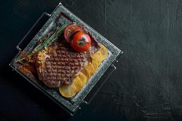Bife grelhado com faca ek esculpida em ardósia de pedra preta. bife em uma pedra de mármore quente. moda de comida escura, copyspace. Foto Premium