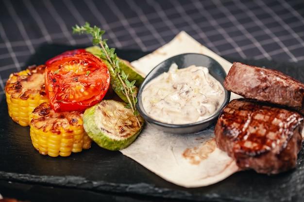 Bife grelhado com legumes no fundo cinza ardósia Foto Premium