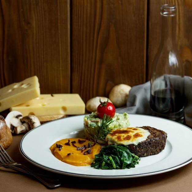 Bife grelhado com queijo derretido e purê de legumes Foto gratuita