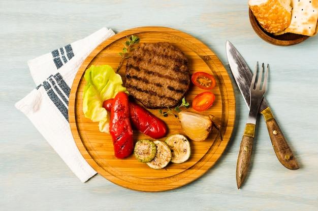 Bife grelhado e legumes servindo na bandeja de madeira Foto gratuita