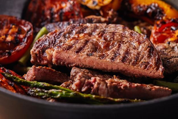 Bife grelhado em uma panela preta com legumes cozidos Foto Premium
