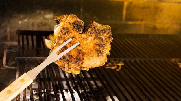 Bife marrom dourado grelhado no garfo Foto gratuita