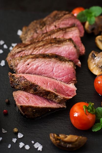 Bife suculento médio raro com especiarias e legumes grelhados. Foto gratuita