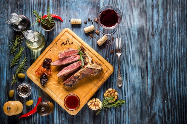 Bife t-bone grelhado raro médio fatiado em fundo de madeira rústico com alecrim e especiarias Foto Premium