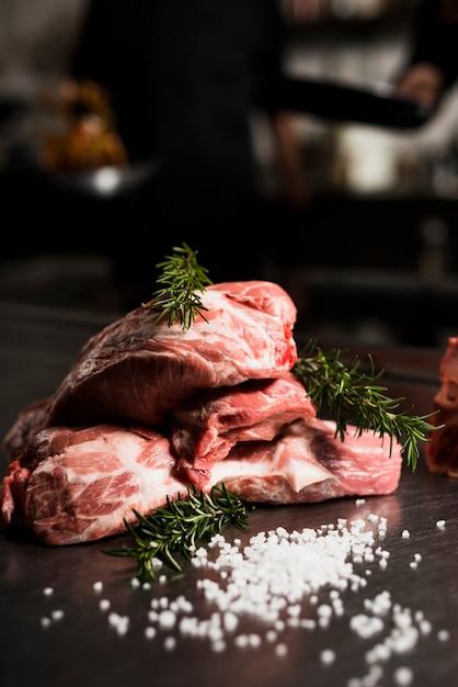Bifes de carne crua com alecrim na mesa Foto gratuita