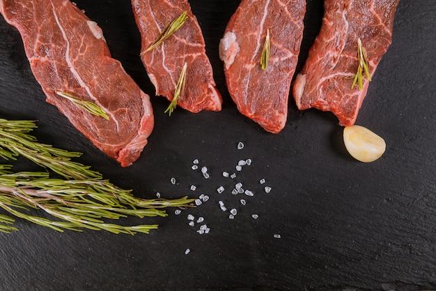Bifes de carne crua com especiarias e alecrim. lay plana. Foto Premium