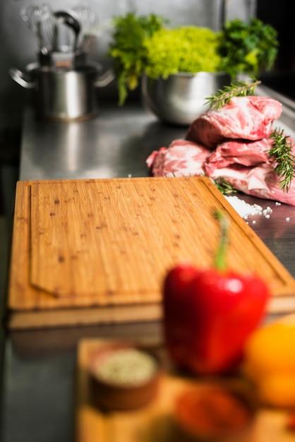 Bifes de carne crua com placa de madeira na mesa Foto gratuita