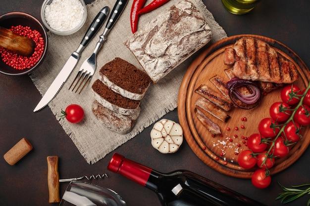 Bifes de porco grelhado fatiado com garrafa de vinho, copo de vinho, saca-rolhas, faca, garfo, pão preto, tomate cereja, alho Foto Premium