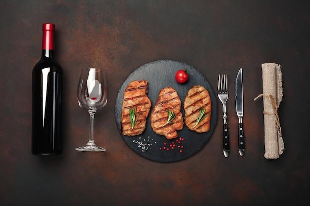 Bifes de porco grelhado na pedra com garrafa de vinho, copo de vinho, faca e garfo em fundo enferrujado Foto Premium