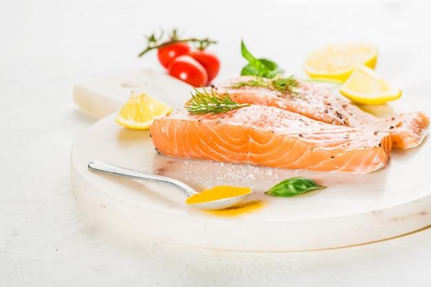 Bifes de salmão crus saborosos colocados a bordo Foto gratuita