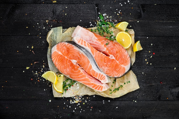 Bifes de salmão na vista superior de fundo preto de madeira Foto Premium