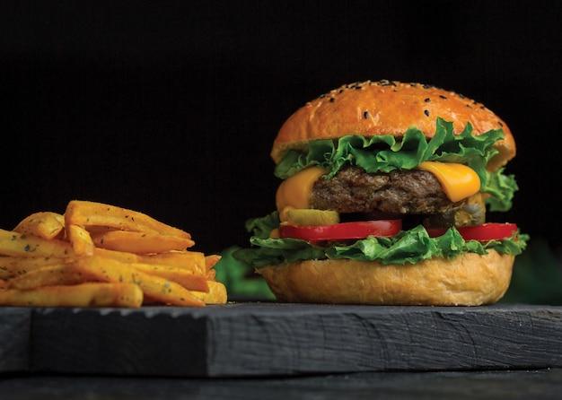 Big mac hambúrguer e batatas fritas em uma placa de madeira escura. Foto gratuita