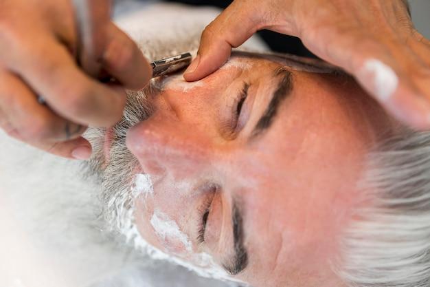 Bigode de barbear de barbeiro para cliente em salão Foto gratuita